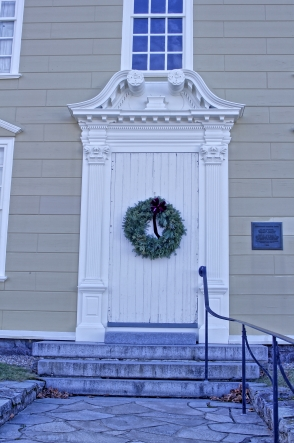 The primitive door with the rococo surrounds.